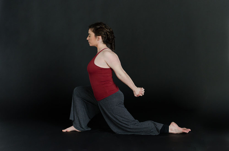 A woman posing in a deep lunge with her eyes closed during her in-studio commercial photo session with Tanis Saucier Photography