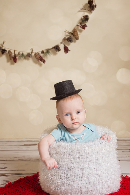 a sweet 10 month old boy sits in a white snowy basket with top hat on his head during his holiday photo session with Tanis Saucier Photography in Montreal