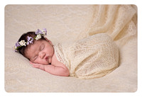 side-lying-newborn-baby-girl-with-flower-halo