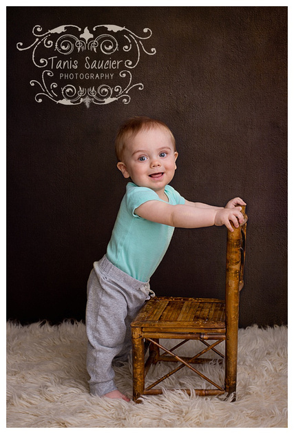 A 10 month old boy practices standing during his Children's Photography Session in Montreal.