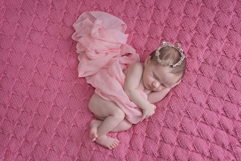 newborn baby girl on a textured knit blanket wearing a sheer pink wrap and a tiara