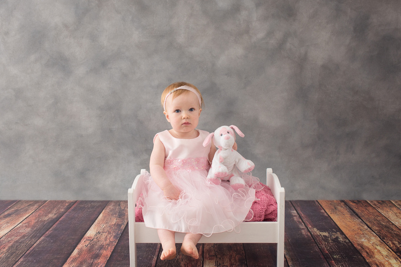 A sweet and classic image of a one year old baby girl sitting on a little bed with her stuffed dog during her children's Milestone portrait session with Tanis Saucier Photography in Montreal.