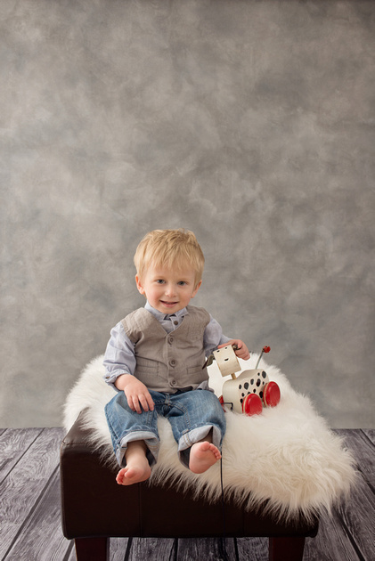 A little boy sits on a white fur rug with a little wooden toy dog in a studio portrait session with Tanis Saucier Photography.
