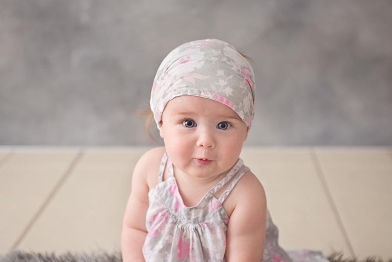 A sweet expression from a 7 month old girl during her milestone photo session with Tanis Saucier Photography in Montreal