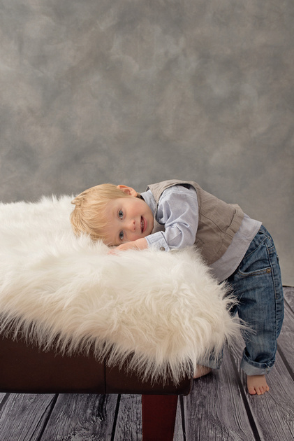 A boy lies on a white fur rug during his studio portrait session with Tanis Saucier Photography in Montreal.