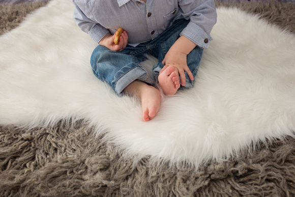 An image of little boy's feet on a white fur rug during his Milestone Portrait Session in Montreal with Tanis Saucier Photography.