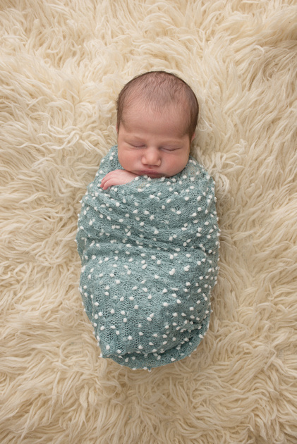 A newborn baby boy swaddled up in a blue wrap sleeping peacefully during his newborn photography session with Tanis Saucier in Montreal