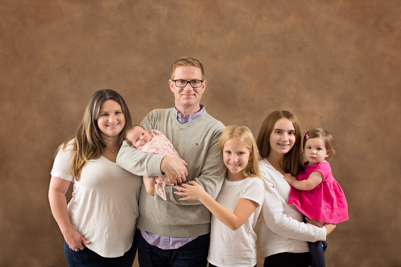 A family photo of a mom, dad and their 4 daughters during their newborn baby girls' portrait session with Tanis Saucier Photography in Montreal.