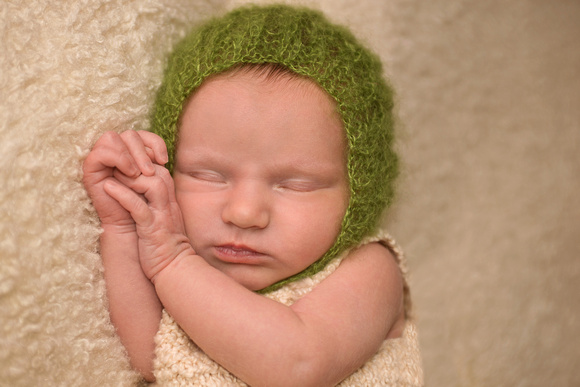 Newborn baby girl, sleeping peacefully on a soft blanket while wearing a knitted dress and soft-green angora bonnet during her newborn photography session in Montreal with Tanis Saucier Photography.