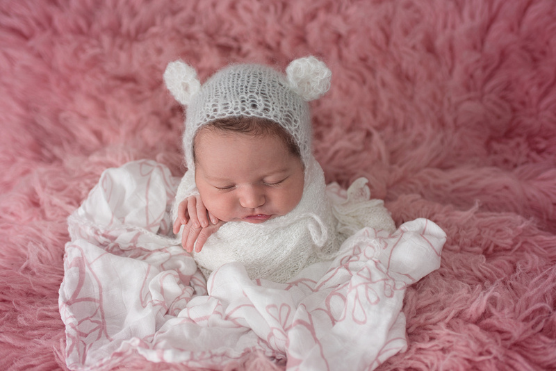 a gorgeous image of a newborn baby girl on a pink flokati rug in the potato sack pose during her newborn portrait session with Tanis Saucier Photography in Montreal, Quebec. http://www.tanissaucier.com