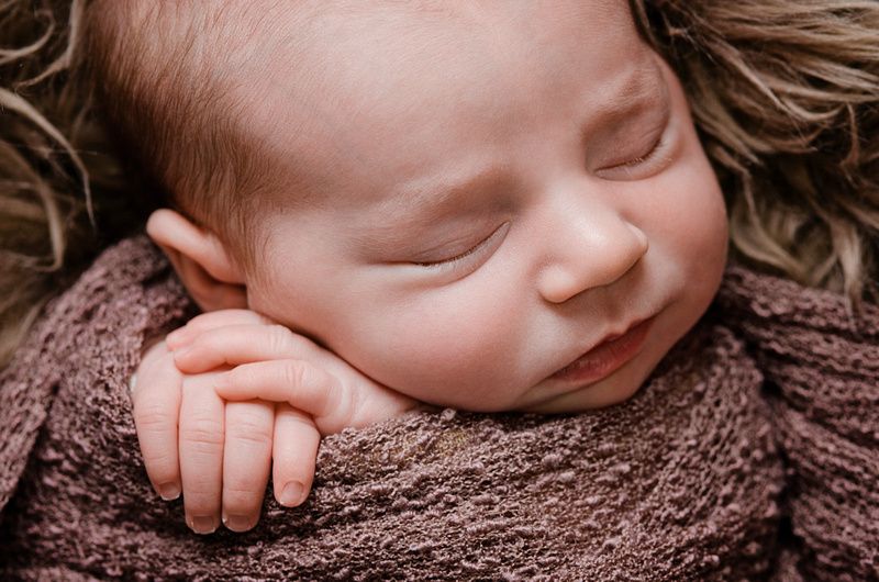 Close-Up of Newborn Baby Girl's Face with Hands Together