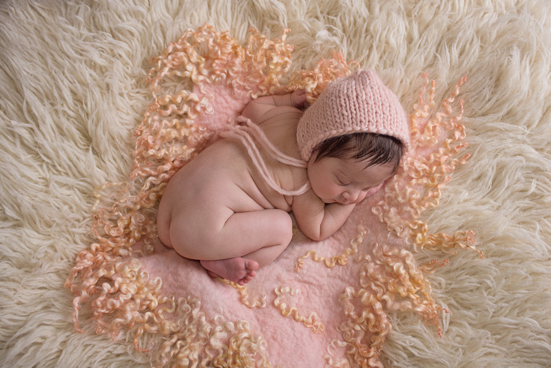 a gorgeous image of a newborn baby girl lying on a peach curly felt and cream flokati rug during her newborn portrait session with Tanis Saucier Photography in Montreal, Quebec. http://www.tanissaucier.com