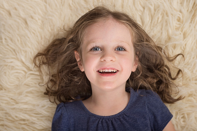 A birds-eye-view of a young girls face with bright eyes and the biggest smile. Taken at Tanis Saucier Photography's studio in Montreal. #heartfeltchildhood www.tanissaucier.com