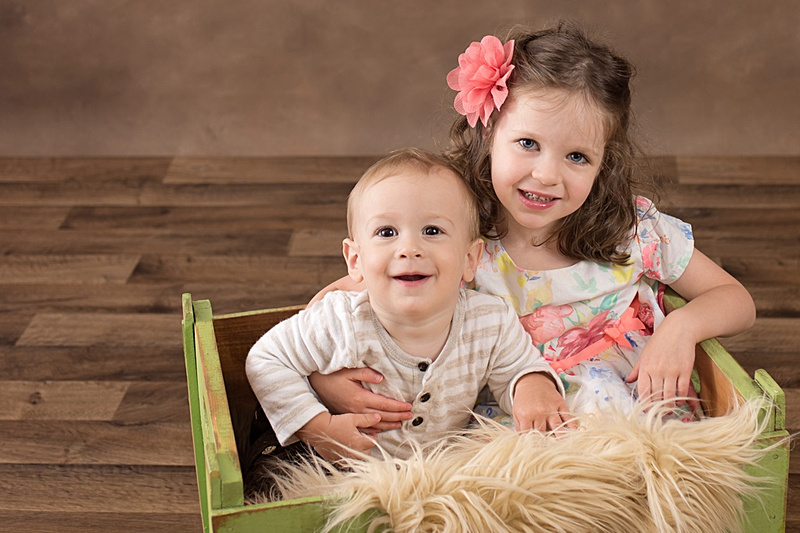 A big sister and baby brother are cuddled up in a green crate looking adorable for their children's portrait session. www.tanissaucier.com #heartfeltchildhood
