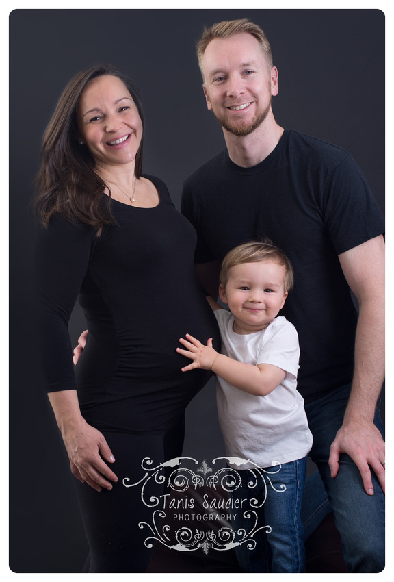 A montreal maternity family portrait with an excited brother-to-be smiling while hugging his mama's belly at Tanis Saucier Photography Studio in Montreal.
