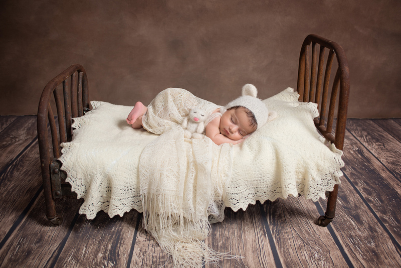 A sweet 6 weeks-new baby girl is sleeping on an antique bed and wearing a soft beige bear bonnet during her newborn photography session with Tanis Saucier in Montreal www.tanissaucier.com