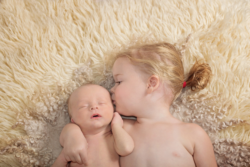 A sweet image of a big sister cuddling and kissing her newborn baby brother while they lay on a cream flokati rug during her newborn portrait session with Tanis Saucier Photography.