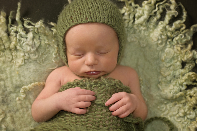 a gorgeous image of a newborn baby boy lying on a green curly felt and wearing a green wrap and matching bonnet during his newborn portrait session with Tanis Saucier Photography in Montreal, Quebec. http://www.tanissaucier.com