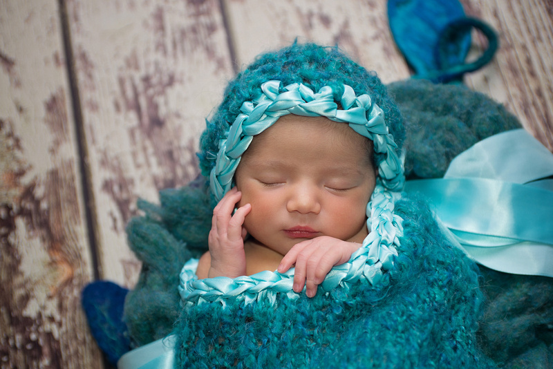 A gorgeous newborn baby girl sleeps in a sea of teal fluff, wrap and bonnet during her newborn session with Tanis Saucier Photography in Montreal, Quebec