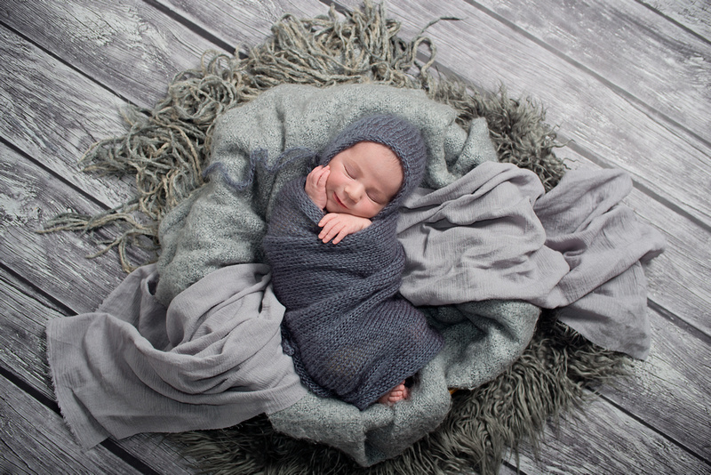 a gorgeous image of a newborn baby boy swaddled in grey ...