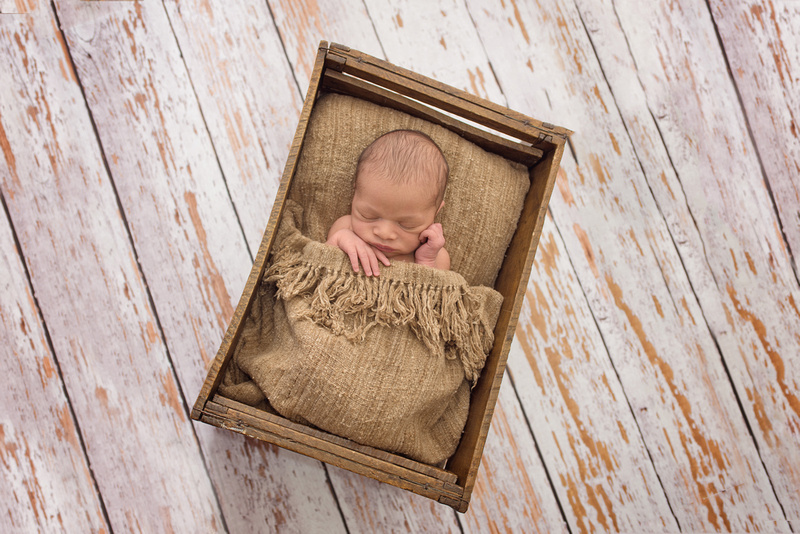 "Newborn photography session highlighting the ""Sleepy Time"" pose in a crate prop at Tanis Saucier Photography's studio in Montreal."