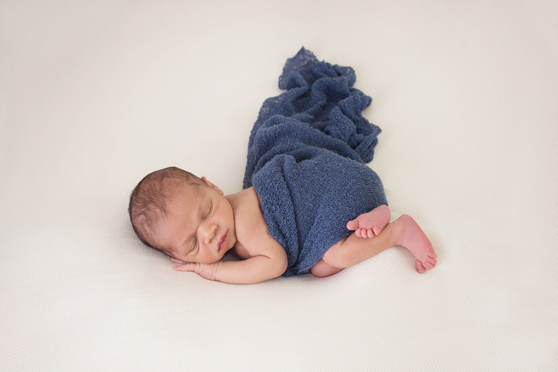 "Newborn photography session highlighting the ""Bum Up"" pose on a sweet baby boy wearing a blue stretch wrap for modesty on the beanbag at Tanis Saucier Photography's studio in Montreal."