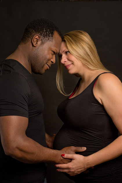 A beautiful mixed couple stare lovingly into each other's eyes during their maternity photography session with Tanis Saucier Photography in Montreal