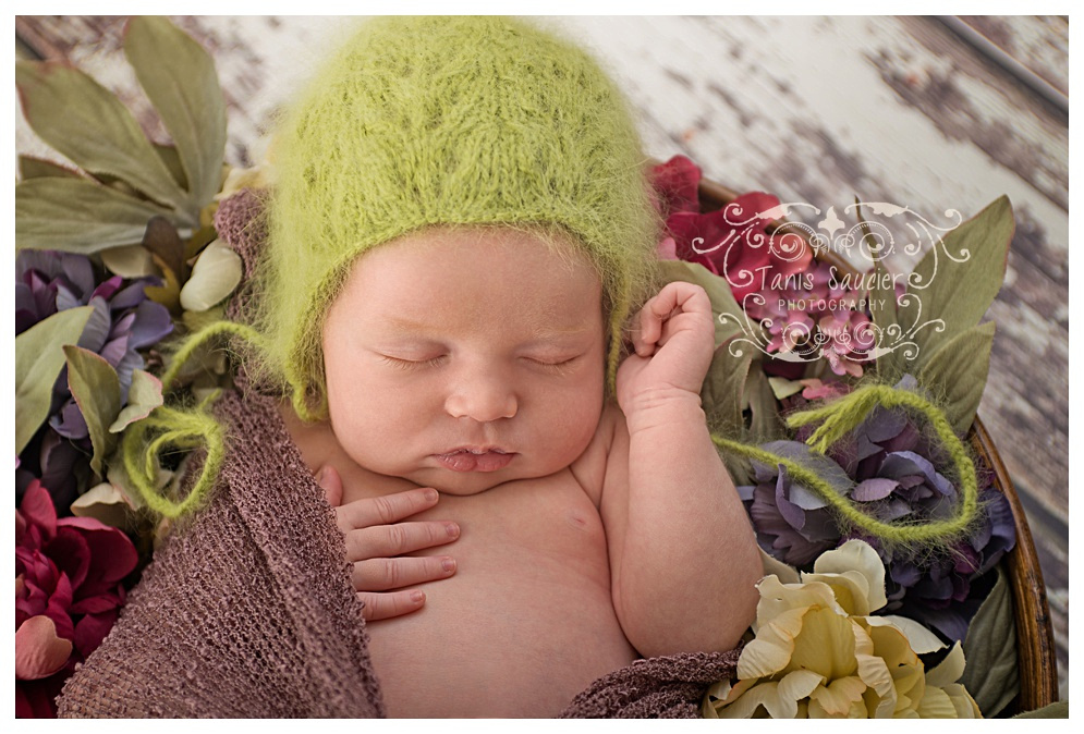 A beautiful 8 days new newborn baby girl is resting in a wreath of flowers during her newborn photography session in Montreal with Tanis Saucier Photography