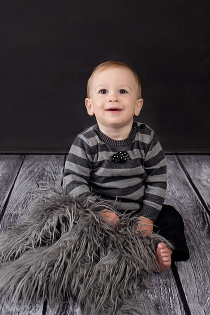 A sweet baby boy looking dapper, dressed in a black and white sweater and black pants. He has a huge smile for his milestone portrait session with Tanis Saucier Photography. www.tanissaucier.com #heartfeltchildhood