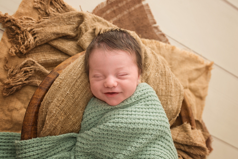 a smiling little newborn baby boy during his newborn portrait session with Tanis Saucier Photography in Montreal