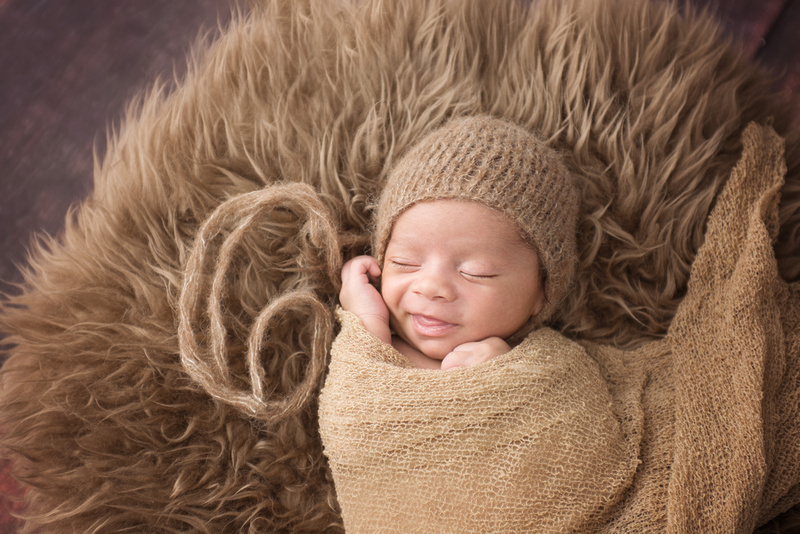 Sweet newborn baby boy smiling during his newborn photo session in montreal with tanis saucier photography