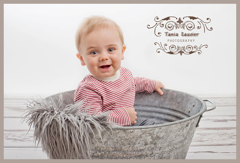 A 10 month old boy sits in a metal wash bin smiling a huge smile during his children's photography session in Montreal