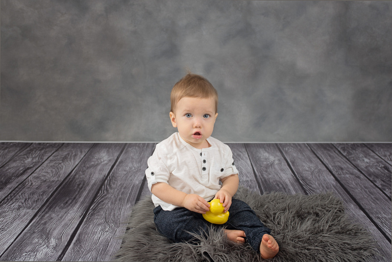 A sweet, one-year old boy sits on a fuzzy grey rug during his 1-year milestone portrait session in Montreal.