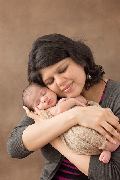 a mama holding her newborn baby girl during her newborn photo session in Montreal